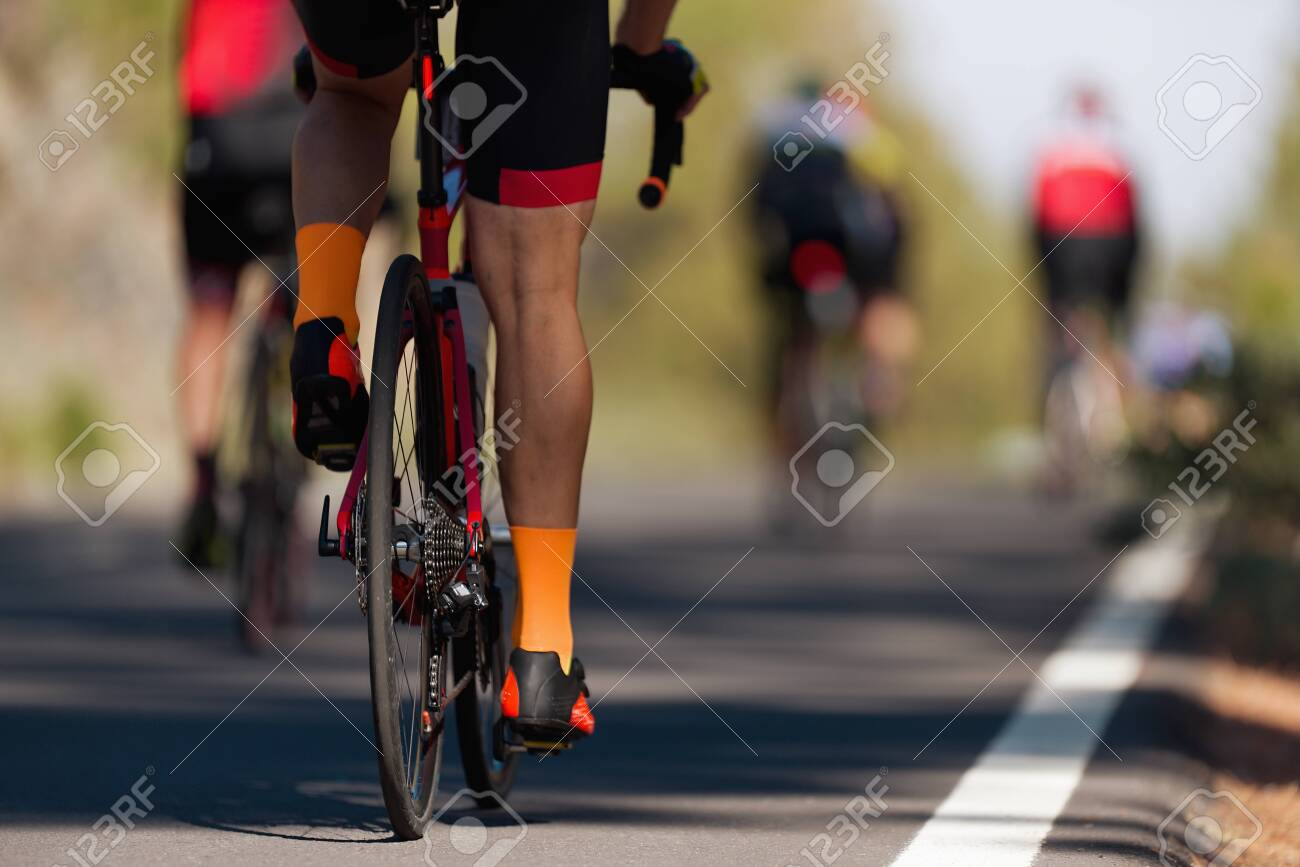 Cycling competition cyclist athletes riding a race at high speed, detail on gear wheels and feet - 138087077