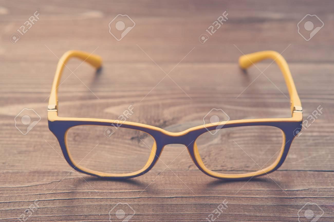 b720b85b1e Foto de archivo - Gafas con marco de gafas de plástico de color amarillo y  vidrio transparente por el que se en una mesa de madera marrón. aspecto  vintage, ...