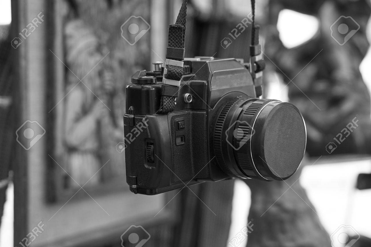 Old retro vintage black film camera with lens attached hanging on a neck strap black