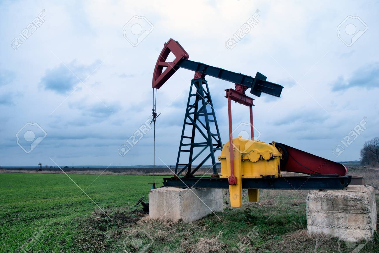 Single oil pump in green field with stormy skies Stock Photo - 17679676