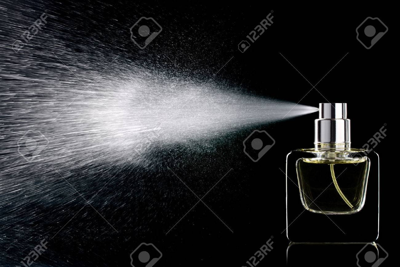 spraying perfume bottle glass on a black background isolated stock