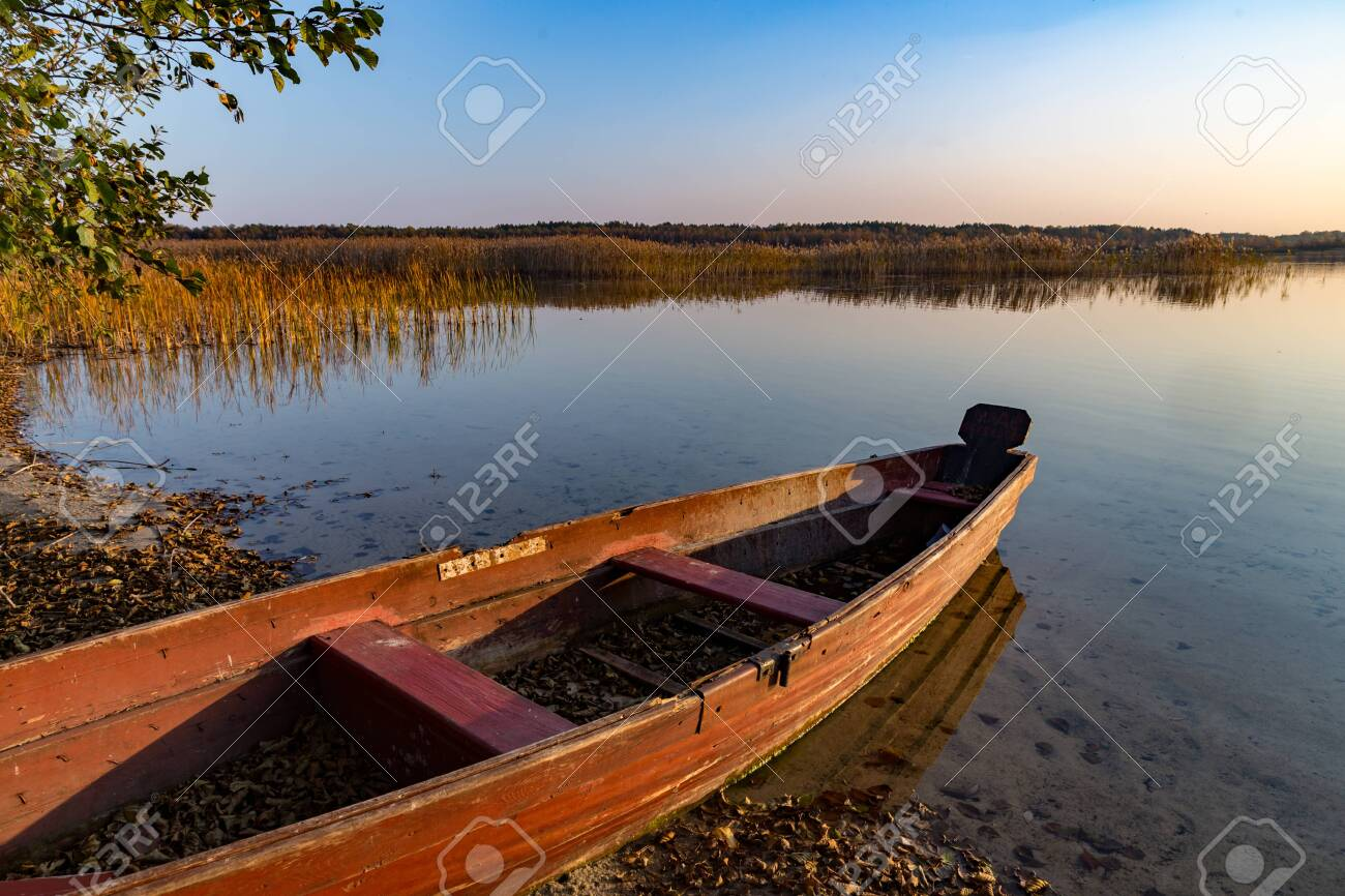old wooden boat on lake. evening landscape, autumn - 130222111
