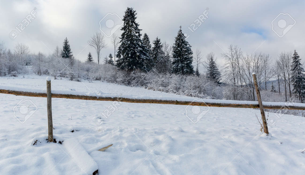 Landscape with wooden fence on winter meadow in mountains - 165451750