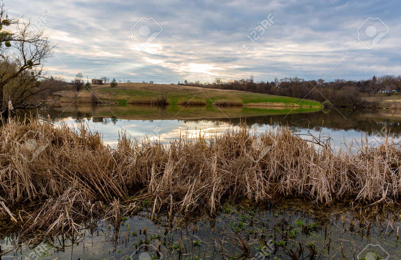 Nice evening scene on wild lake in spring evening. Take it in Ukraine - 168208860