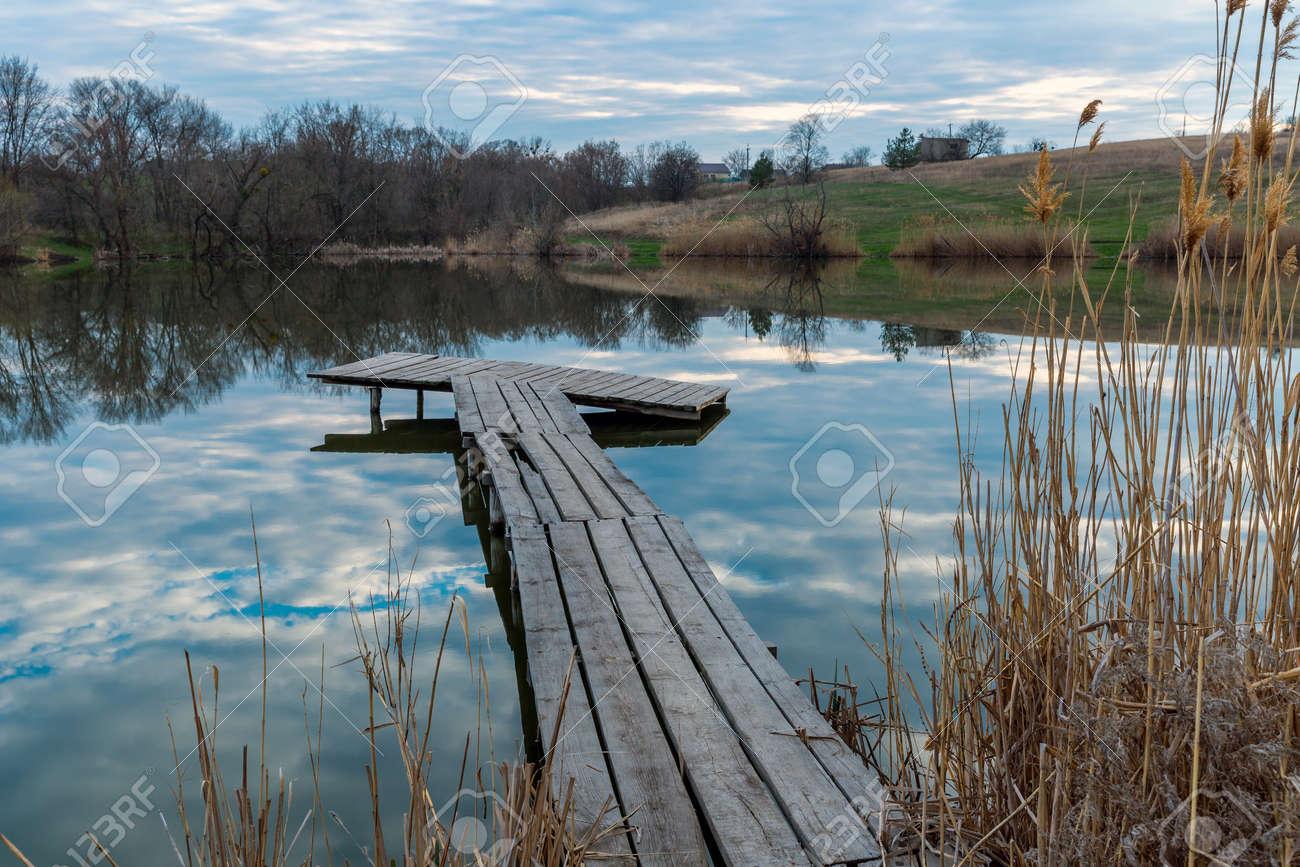wooden firshing bridge on rural lake at evening time - 168208872
