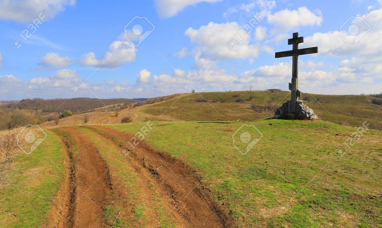 rural road near cross on green hill - 168208874