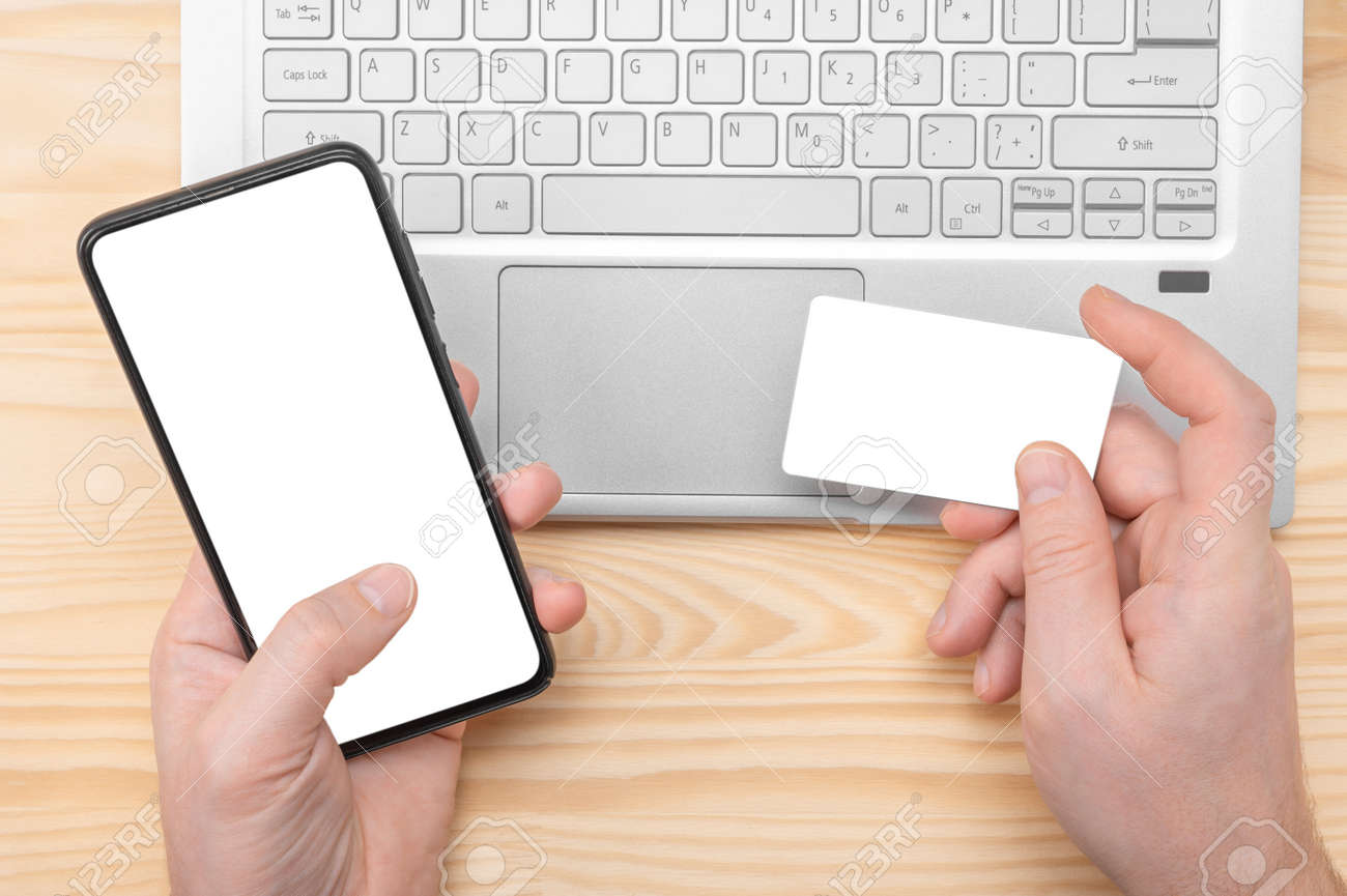 Online Shopping. man hands hold cell phone with blank white screen and mockup credit card on laptop background. man holding credit card using phone and laptop for online shopping making orders at home - 169225049
