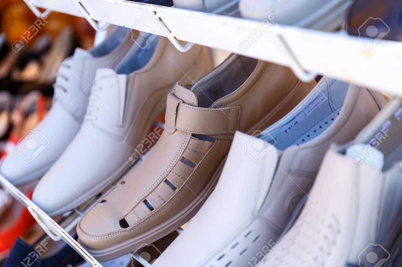 Les chaussures d'été pour hommes et femmes se trouvent sur les étagères des magasins
