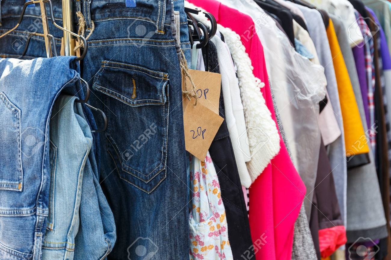 Hangers with men's and women's clothing at the garage sale