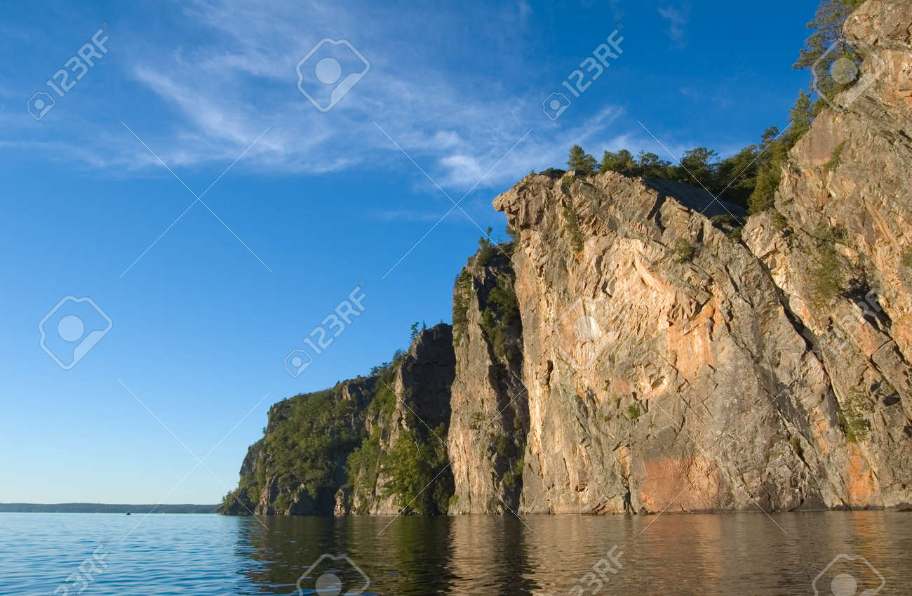 High cliff at shore of Mazinaw Lake in sunset light Stock Photo - 1630243