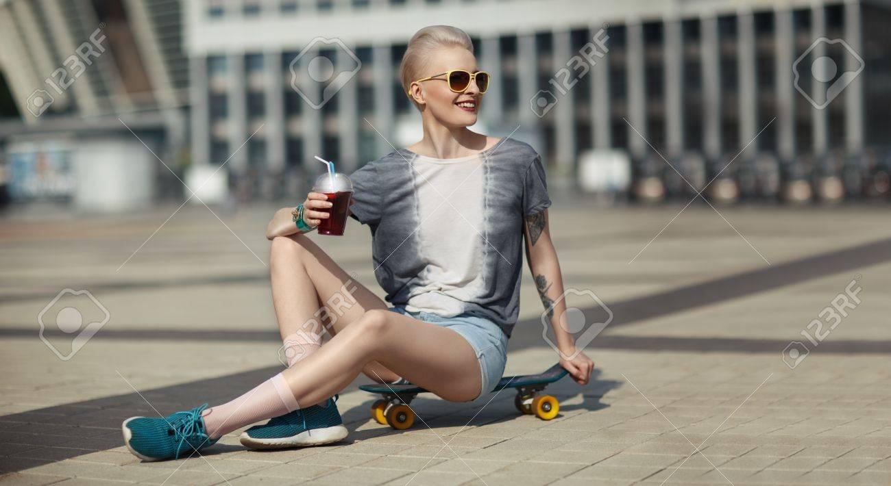 eaa787f0f4 Foto de archivo - Olhar de alta moda. glamour alegre linda jovem loura no  verão brilhante casual hipster roupas sentado em um pouco centavo  skatebord