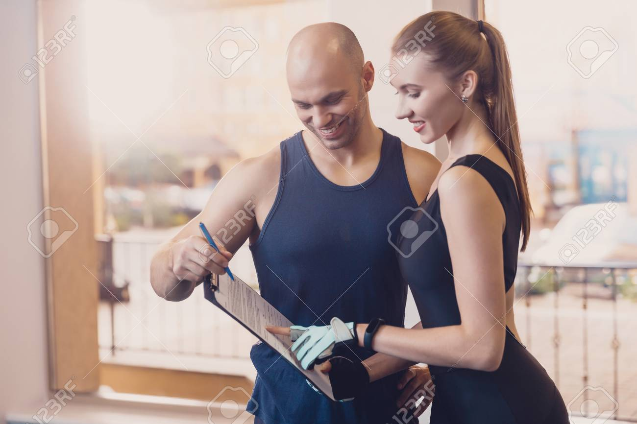 Trainer writes a fitness program training the girl. The program of physical training for effective results when working in the gym. Work on physical labor with an individual trainer in a fitness club. - 121830086