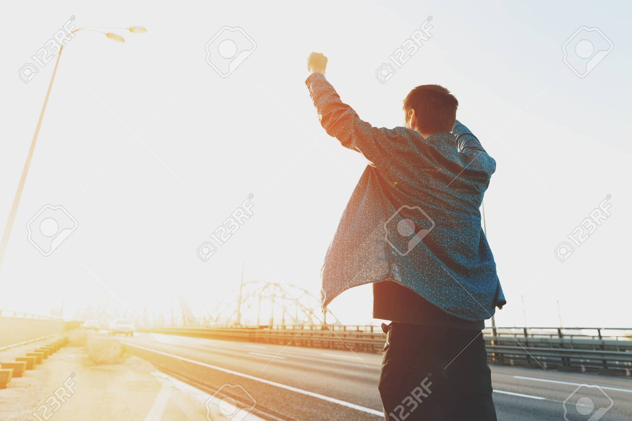 Happy man is standing with his arms raised up. Happy man jumping for joy with his hands up. Happy young man at sunrise on a busy bridge cars. The concept of a free and joyful person - 121830255