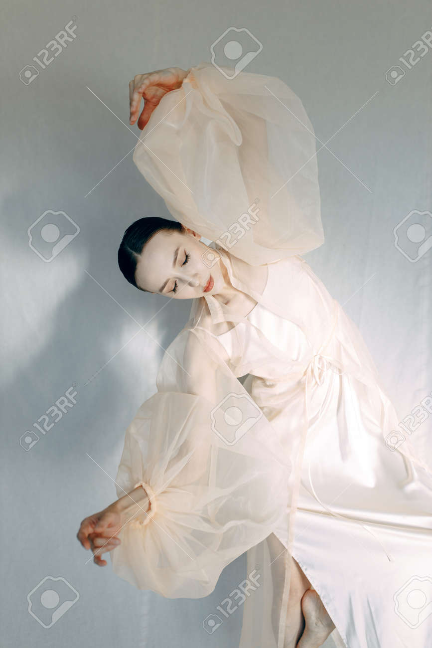 A beautiful girl poses in the studio, in the style of fine art. Fashion art photo of a young sensual lady in a flying dress. - 167192620