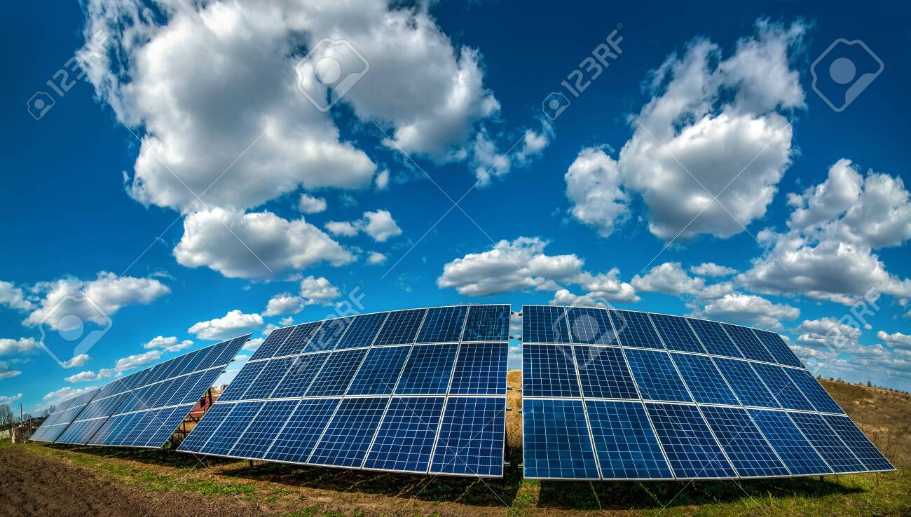 Solar energy station panel system on plowed field and sky with beautiful clouds - 157213917