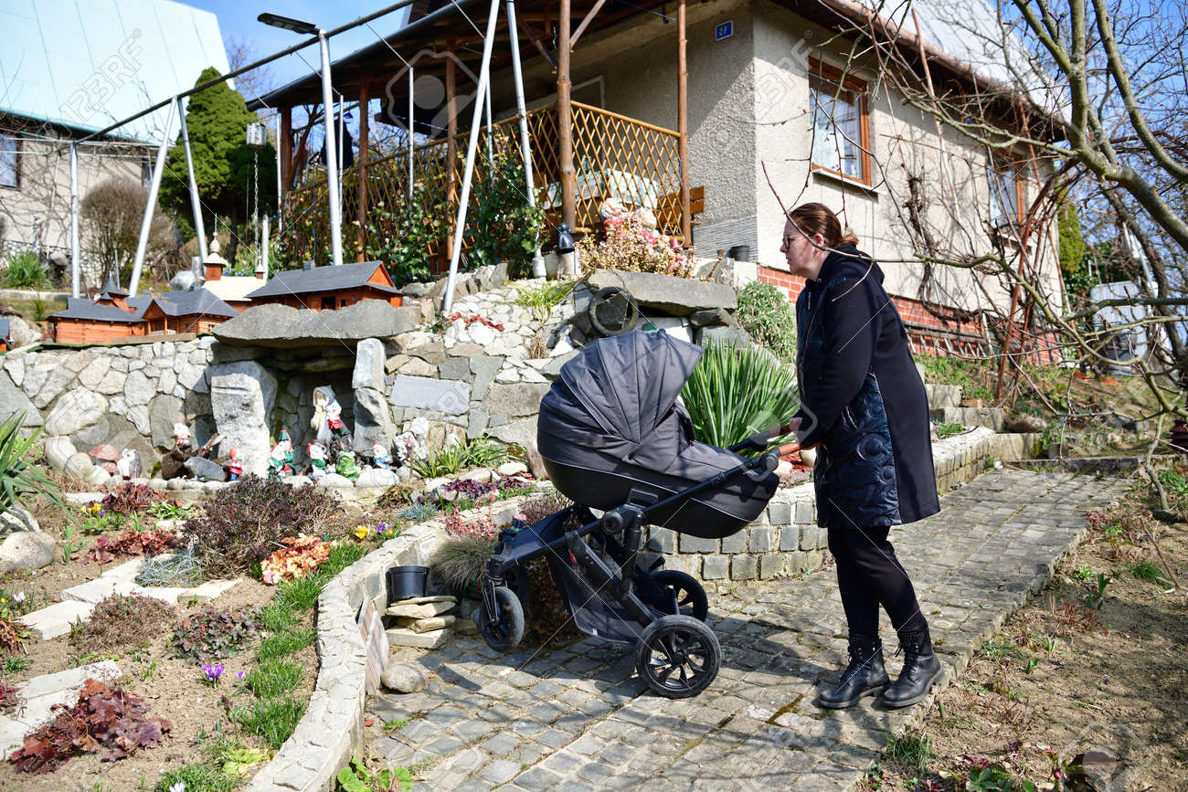 A woman in a black coat walks with a baby buggy carriage around a garden hut - 168381667