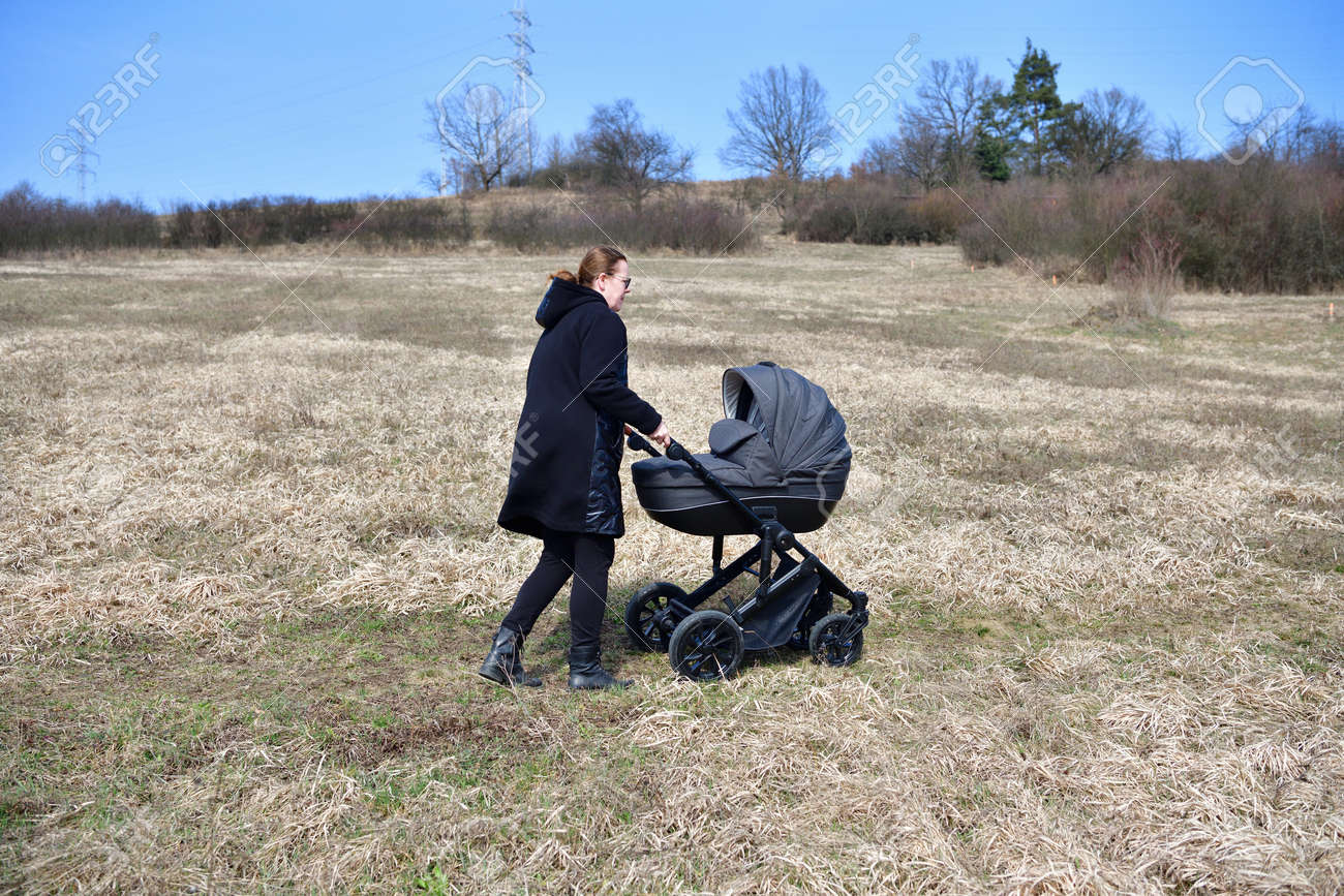 A woman dressed in a black coat on a walk with a baby carriage in the spring nature - 168381668