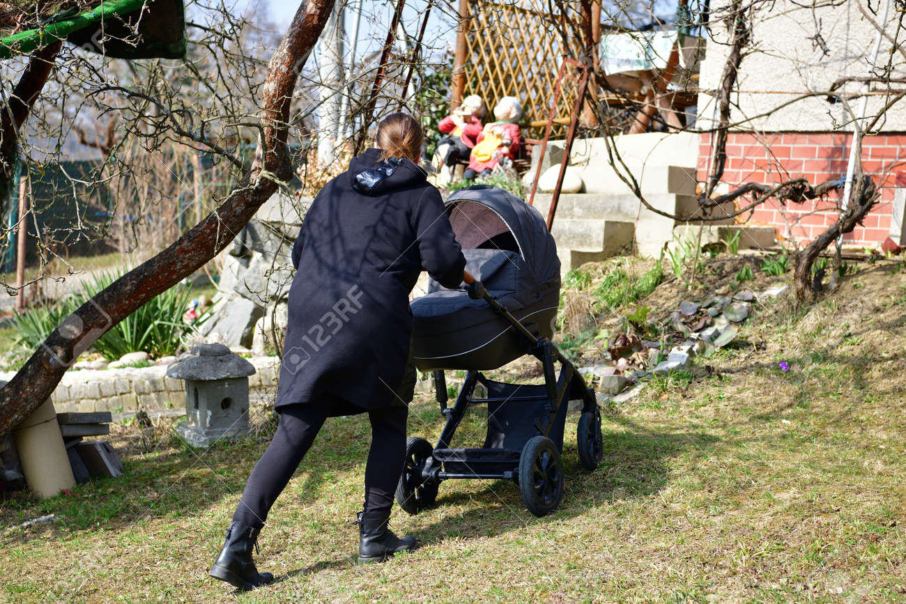 A woman in a black coat walks with a baby buggy carriage around a garden hut - 168381669