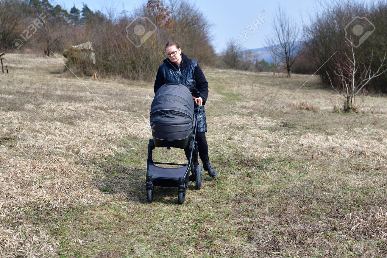 A woman dressed in a black coat on a walk with a baby carriage in the spring nature - 168381784
