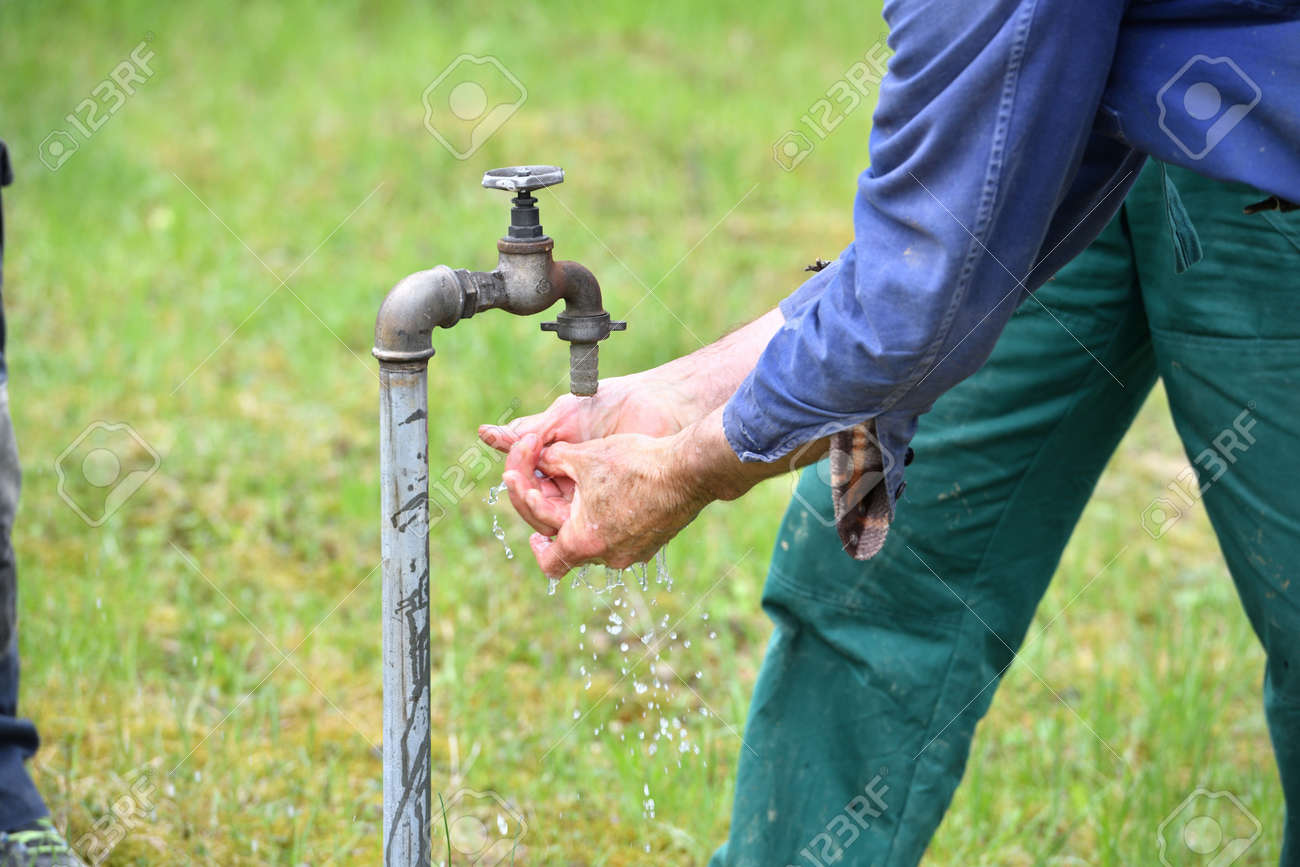 Washing hands on a green meadow from the water supply of a well - 170150014