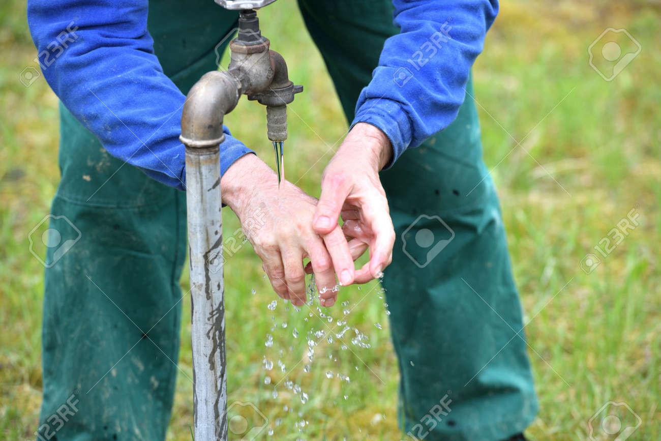Washing hands on a green meadow from the water supply of a well - 170150017