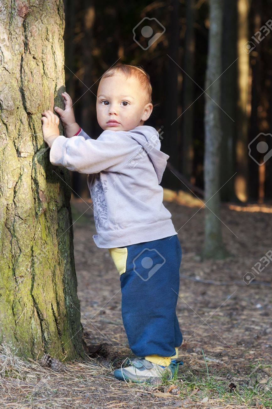 森の木のそばに立って、性格かわいい幼児。 ロイヤリティーフリーフォト