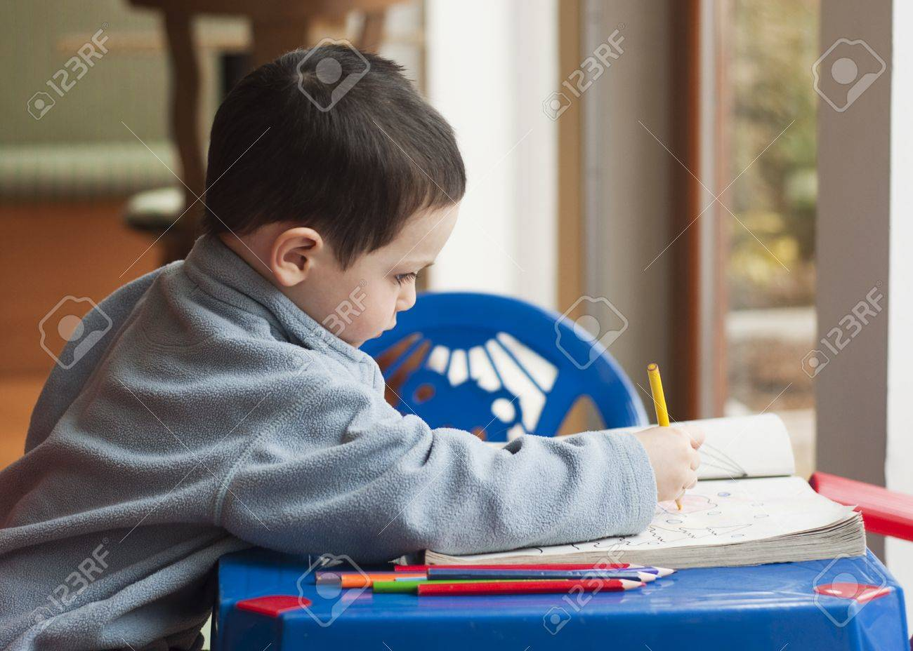 Profile Portrait Of A Small Child Drawing And Coloring Pictures With Colorful Crayons Sitting On