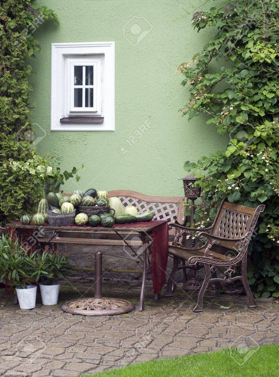 Small Patio Or Street Garden With Rustic Chair And Table, Green Vegetable  And Plants Stock