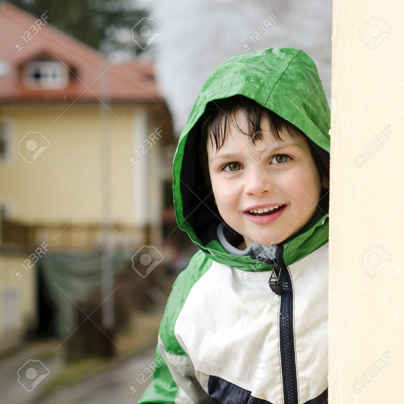3a5d25dc9 Portrait Of A Happy Smiling Child Boy In A Raincoat In The Rain ...