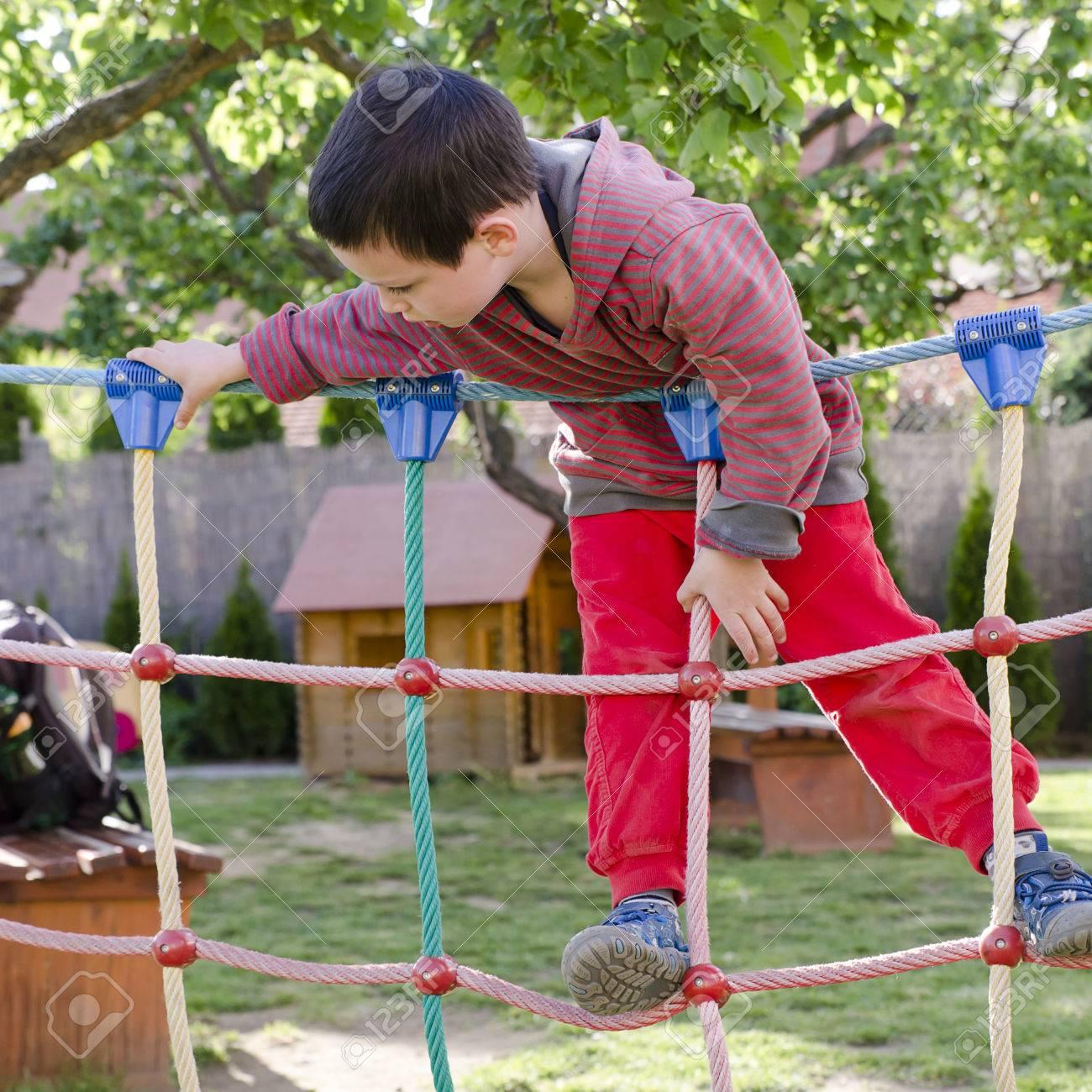 Niño Palying En Parque Infantil, Escalada En Equipos Carrera De ...