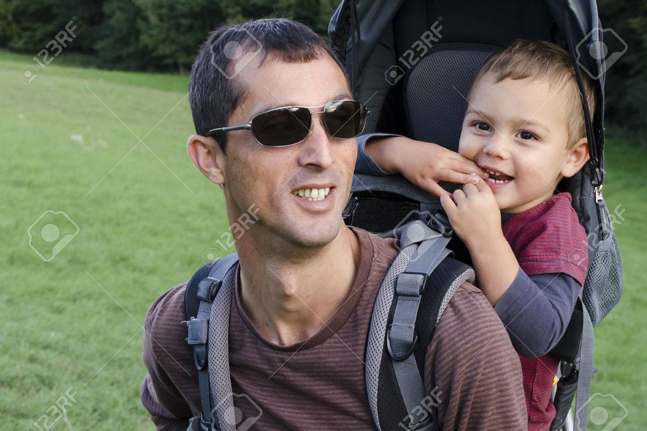 Father Hiking With Child Boy In Backpack Baby Carrier. Stock Photo ...