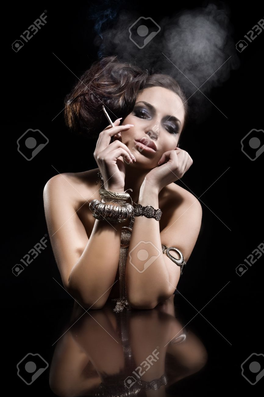 Portrait of beautiful young woman smoking a cigarette  Black background  A lot of jewellery Stock Photo - 17286147