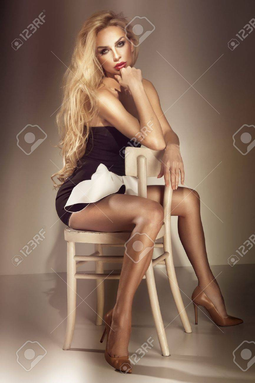 Beautiful elegant woman with long curly hair posing on chair, looking at camera. Stock Photo - 18824333