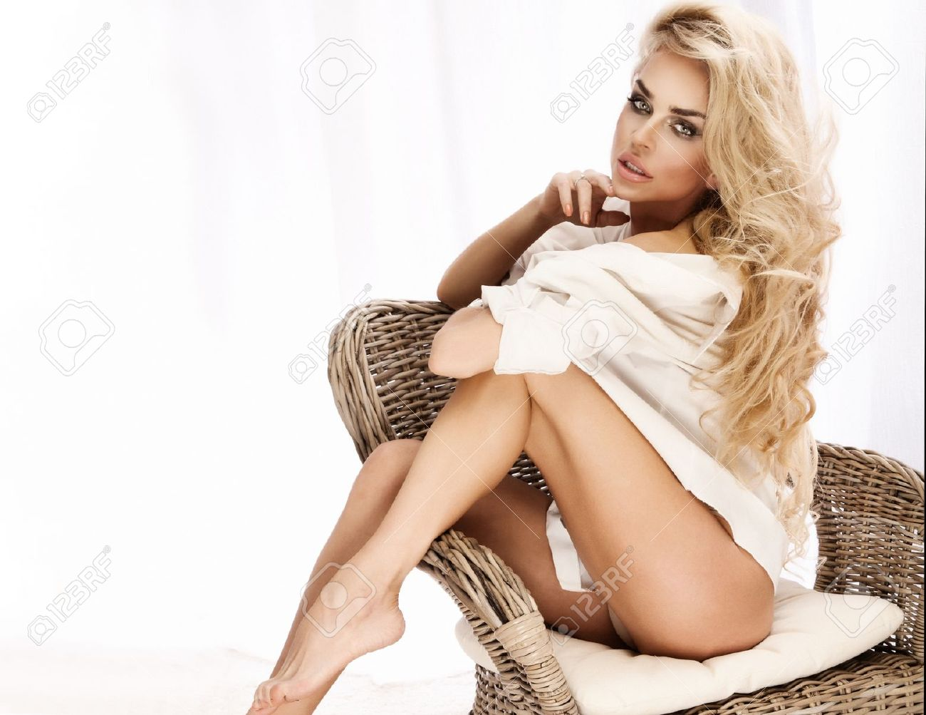 Portrait of beautiful young sexy woman sitting on chair, wearing white shirt. Stock Photo - 18824332