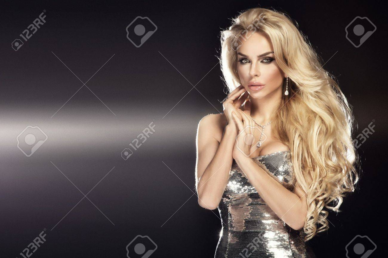 Fashion picture of beautiful young blonde woman wearing glitter silver dress. Long healthy curly hair. Stock Photo - 18824334