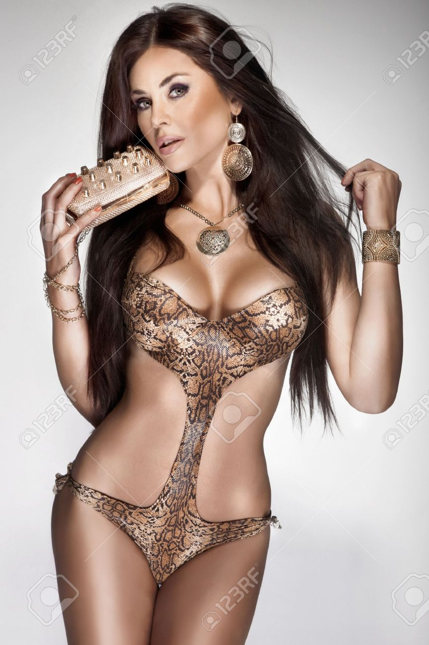 Attractive brunette young woman with long healthy hair posing in fashionable swimsuit. A lot of gold jewellery. Perfect body. Stock Photo - 19061665