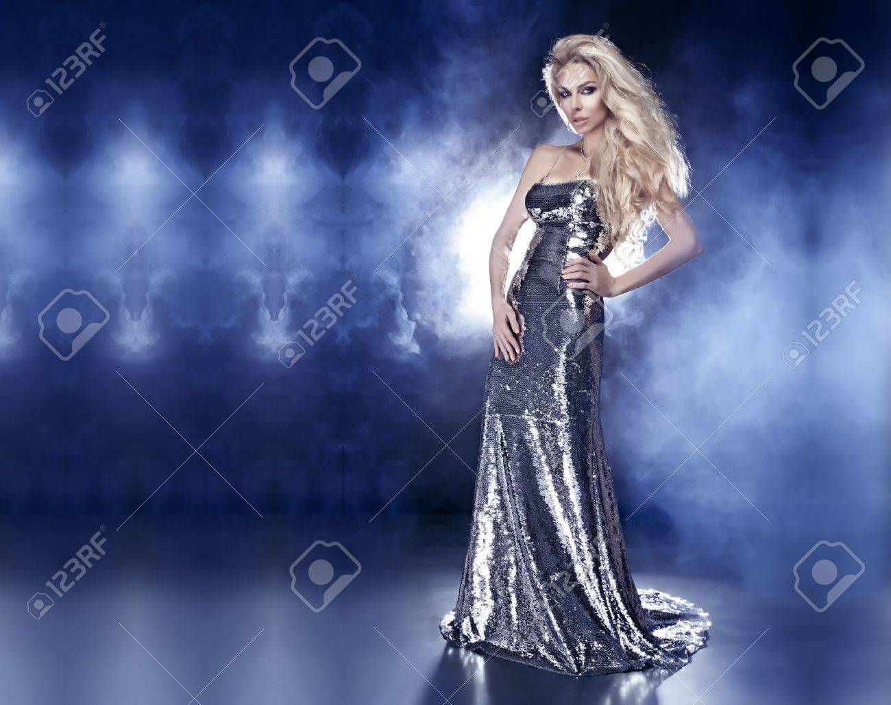 Beautiful young blonde woman posing in fashionable silver evening dress over the dark interior Stock Photo - 19502178