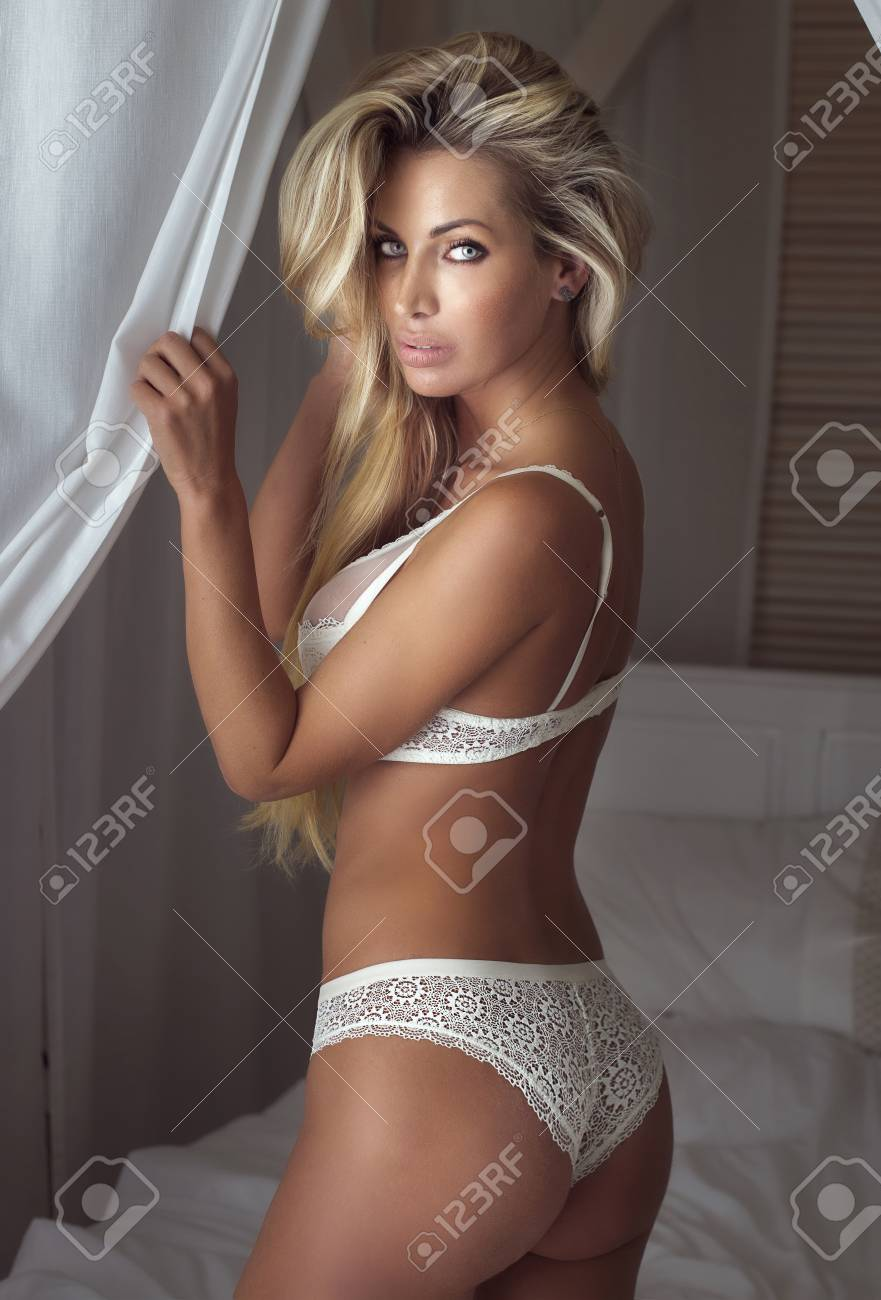 d19c41255 Beautiful sexy blonde woman in lingerie posing in bedroom. Ideal body. Stock  Photo -