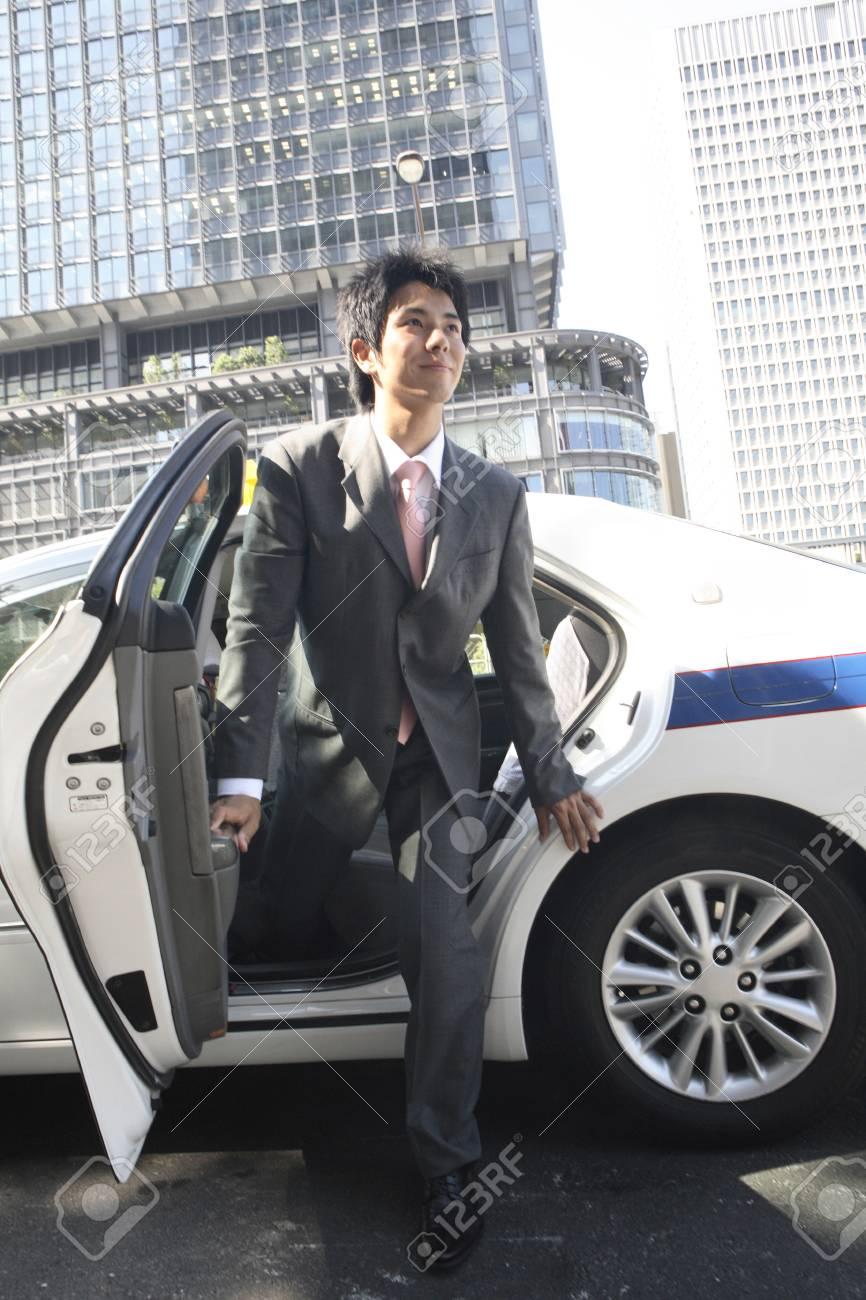 ビジネスマンがタクシーから降り...