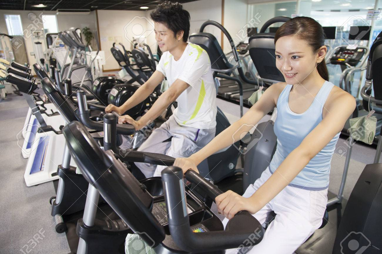 Men and women to train in the exercise bike Standard-Bild - 49519000