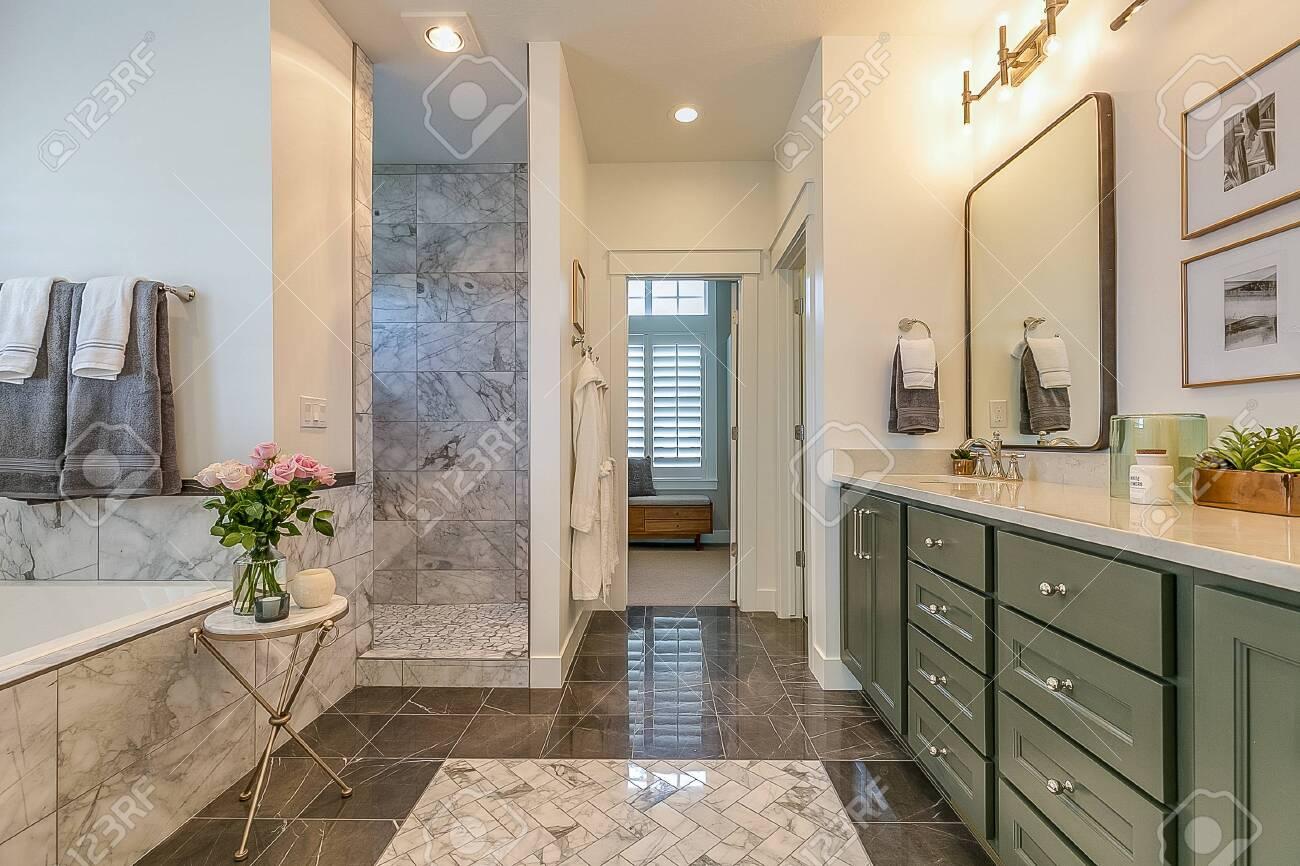 Lovely dark green bathroom cabinets in spa-like master bathroom - 145368590