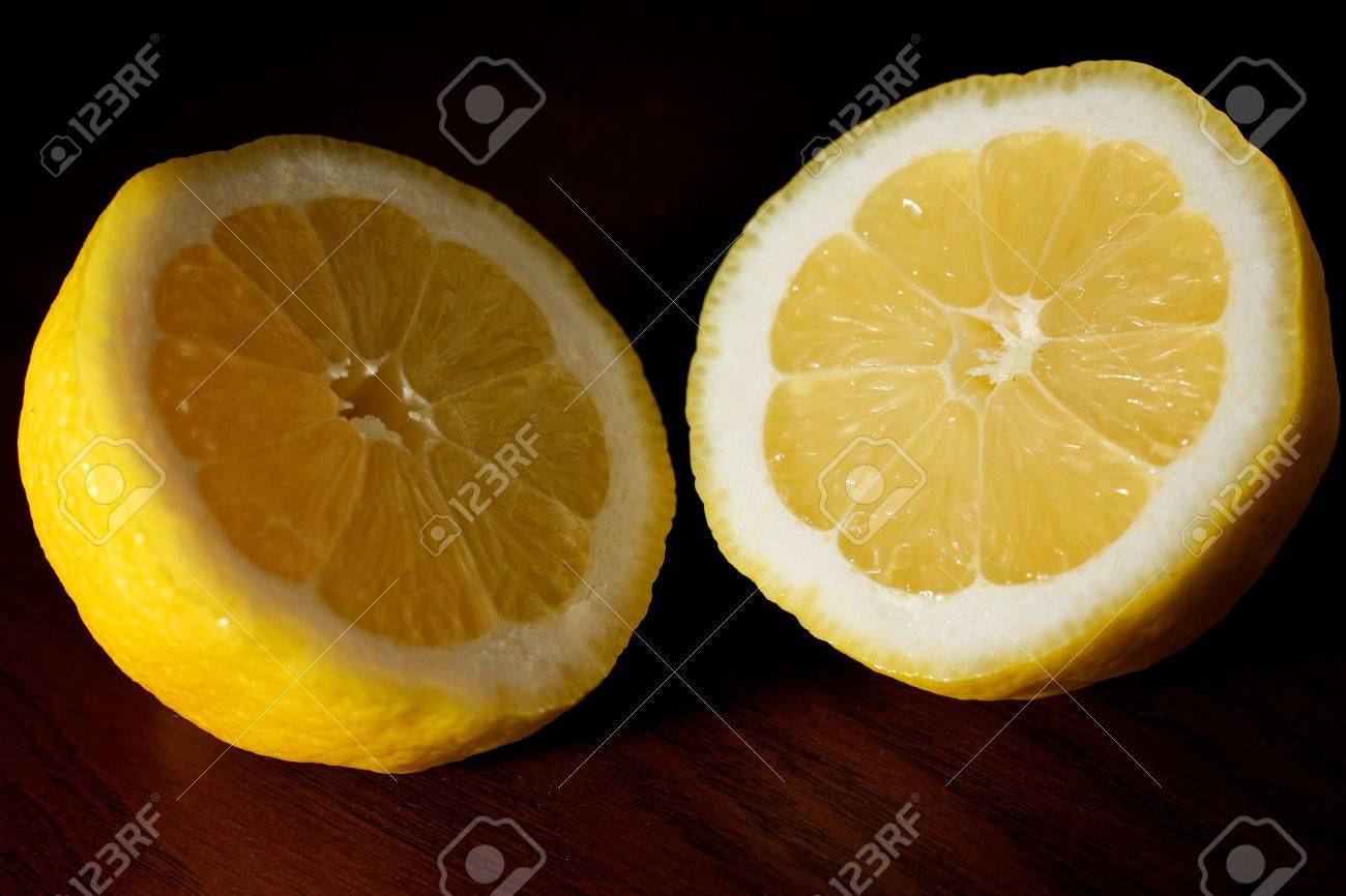 A lemon cut in half, exposing both sides on a table Stock Photo - 9508637
