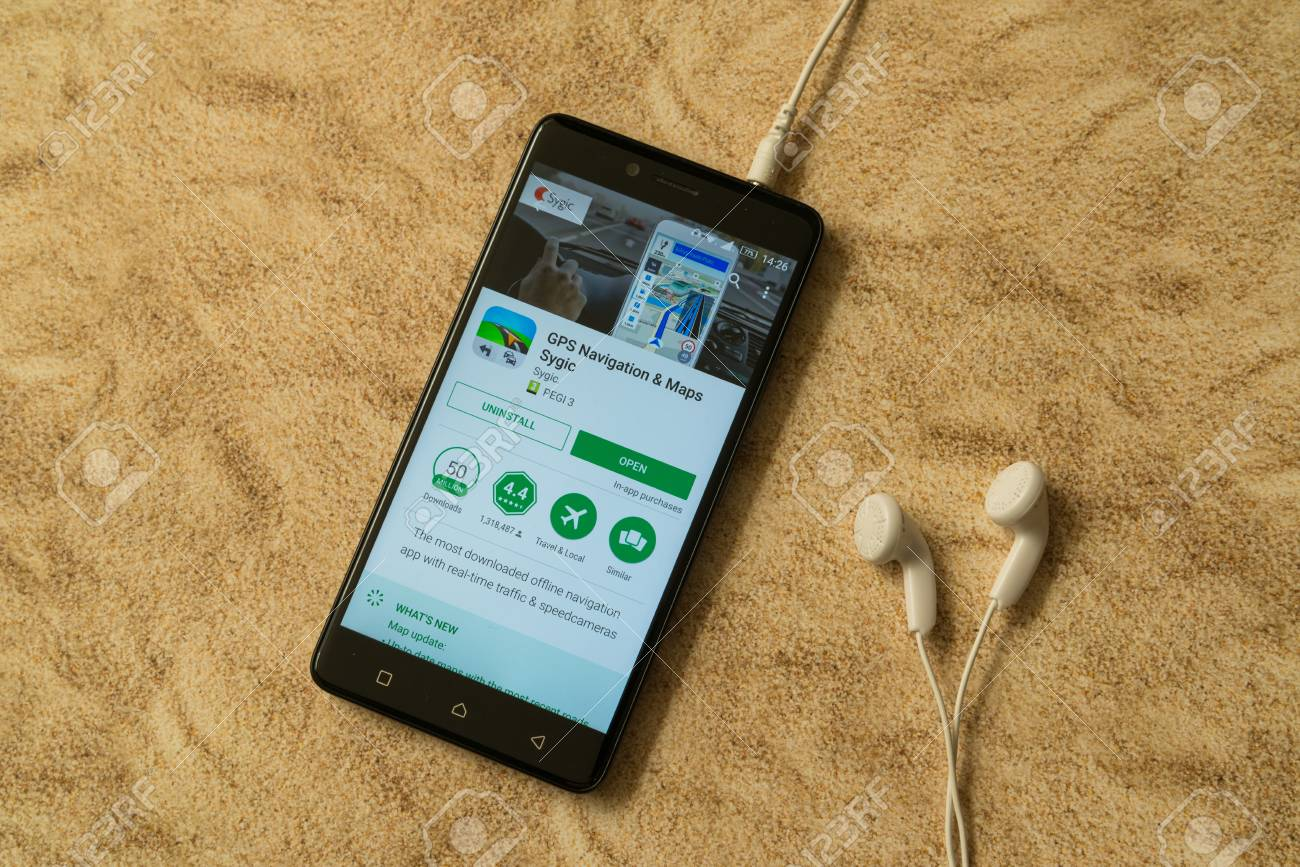 London, november 14, 2017: Sygic application in google play store on sandy  background and earphones