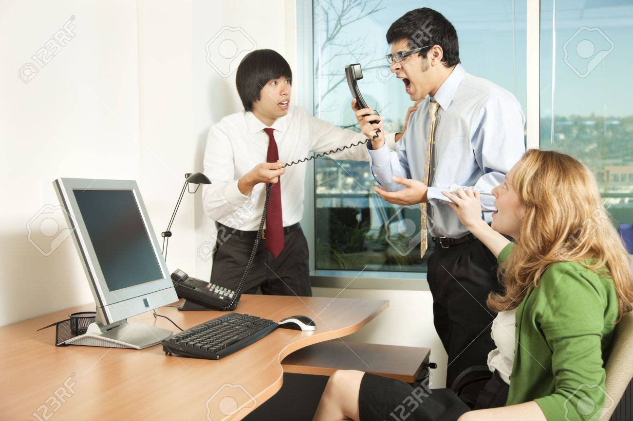Photo of a businessman losing his temper on a phonecall in front of his colleagues. Stock Photo - 4505028