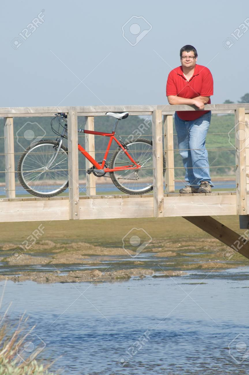 cycler on the seaside over wooden bridge looking to the landscape resting Stock Photo - 7108353