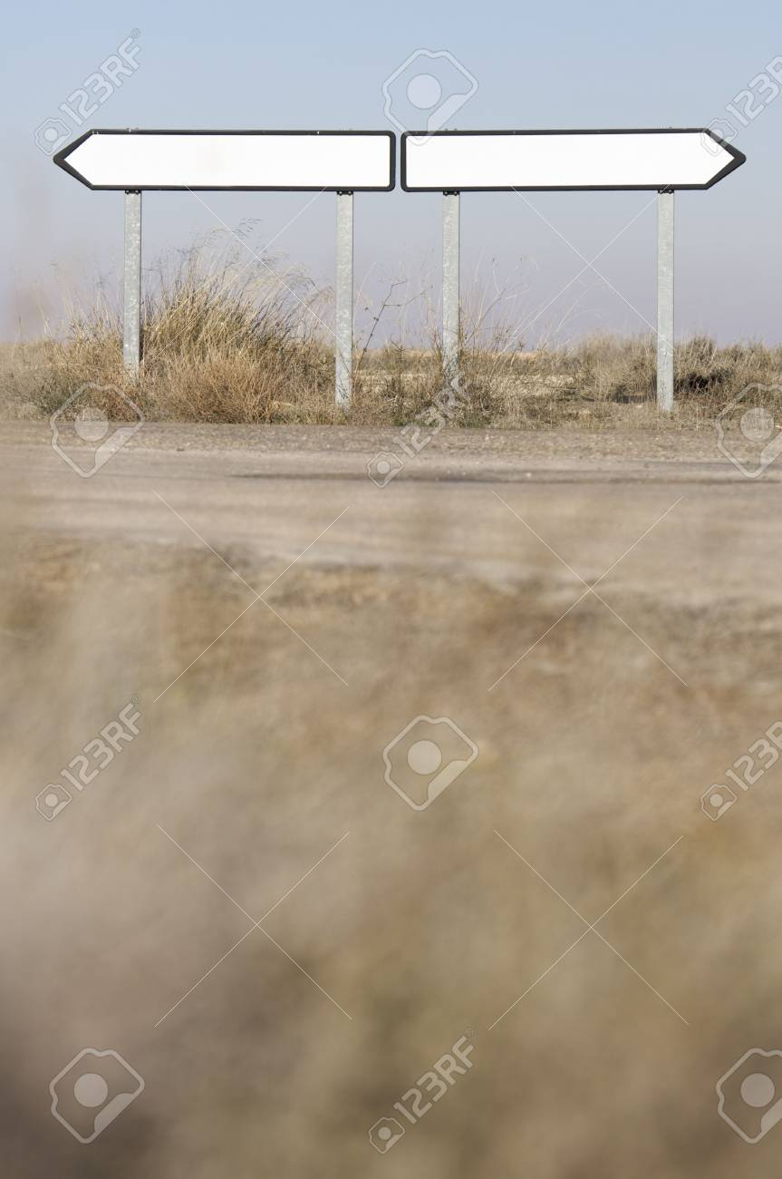 two white traffic signs in a barren landscape Stock Photo - 6434127