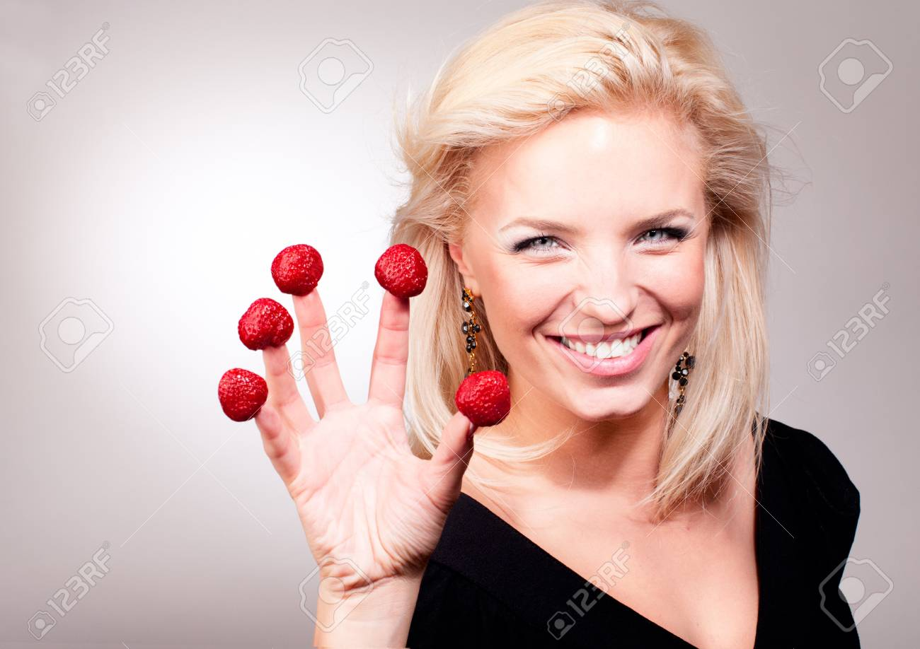 Portrait of blonde woman stick strawberry on fingers Stock Photo - 9959398