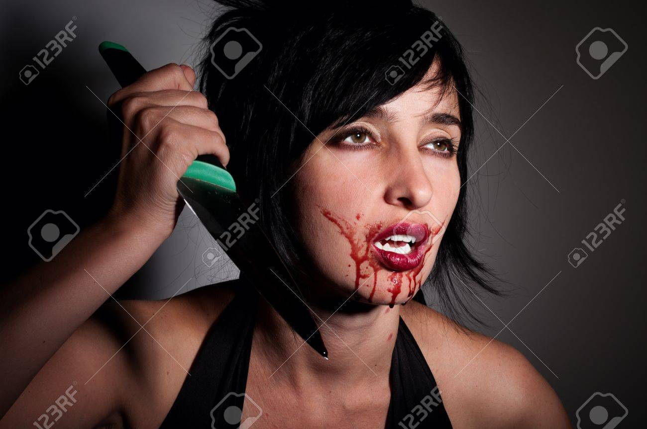 Crazy vampire woman with blood on her face  and knife in hand Stock Photo - 10542215