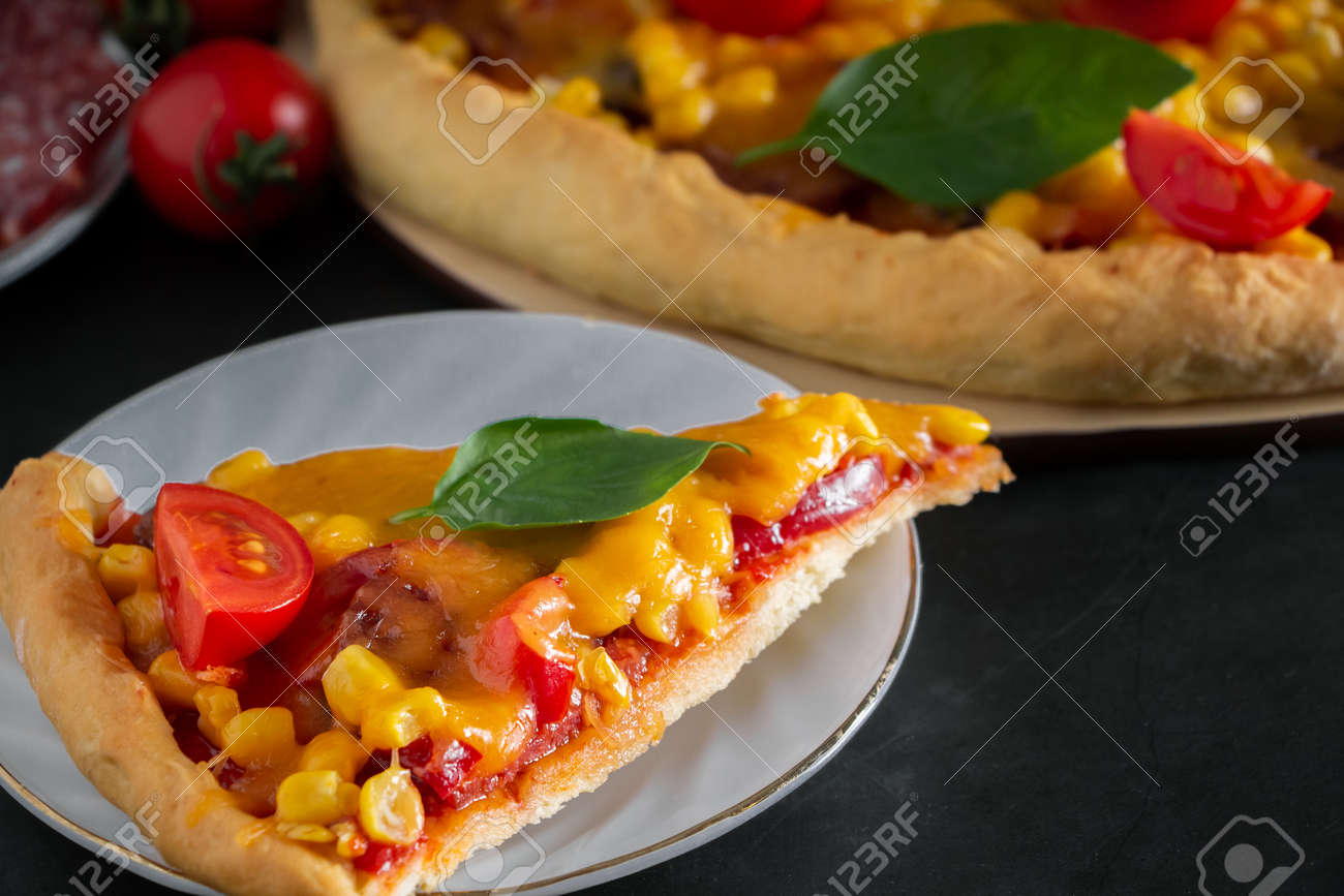 Slice of pizza with cherry and basil on a black background. Ingredients for preparing national Italian food. Tasty freshly prepared pizza with cherry tomatoes and green basil on a black background. Vertical photo, place for text. - 159214445