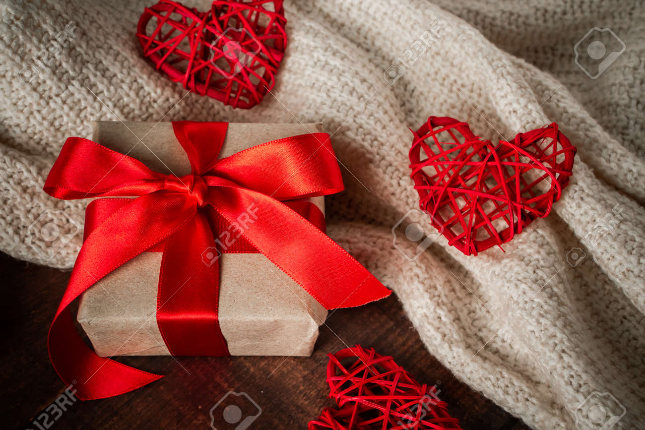 Valentines day surprise in box with red ribbon. Gift for lovers on the background of handmade hearts and a white knitted sweater - 155052526